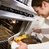 Cook removing roast beef from oven