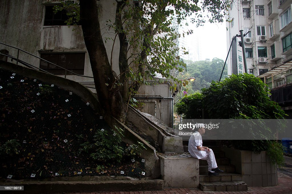 A cook sits near some steps while holding a cigarette in the Tai Hang area of Hong Kong, China, on Saturday, March 30, 2013. Rents are climbing in neighborhoods near Causeway Bay and Hong Kong's other prime shopping districts, known for luxury stores that attract free-spending tourists from mainland China. That's squeezing out mom-and-pop shops, congee and noodle vendors as developers and landlords seek to profit from the trend. Photographer: Lam Yik Fei/Bloomberg via Getty Images
