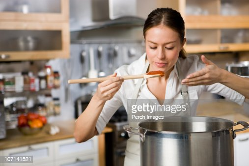 Cook smelling and tasting sauce