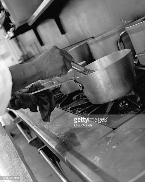 Cook stirring food in a pot