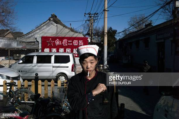A cook takes a break with a cigarette in Beijing on March 7 2017 Prices for goods at the factory gate in China beat expectations slightly in February...