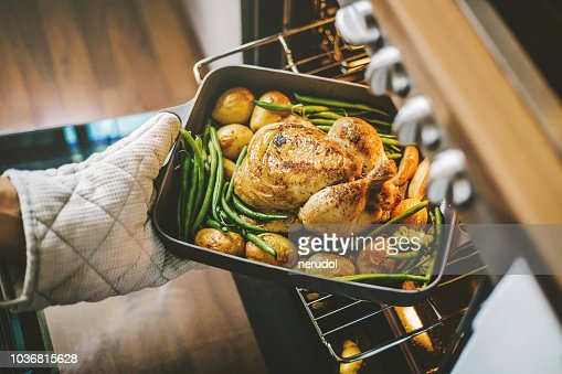 Cook taking ready chicken from the oven : Stock Photo