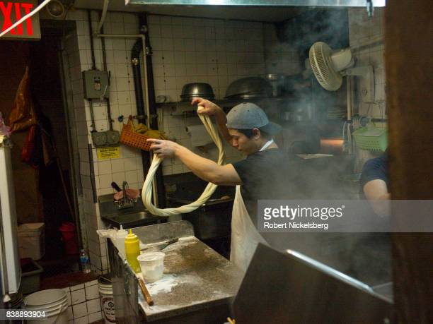 A cook twirls and twists dough that he will cut to make fresh handpulled noodles August 12 2017 at the Tasty HandPulled Noodle restaurant in New York...