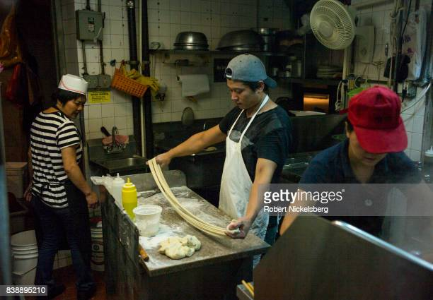 A cook twists and stretches dough that he will cut to make fresh handpulled noodles August 12 2017 at the Tasty HandPulled Noodle restaurant in New...