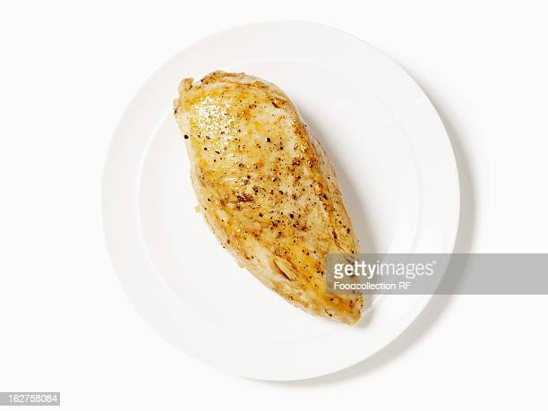 Cooked boneless skinless chicken breast on white plate