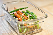 Close-up of cooked carrots, green beans and sliced almonds in clear class crockery container on kitchen counter