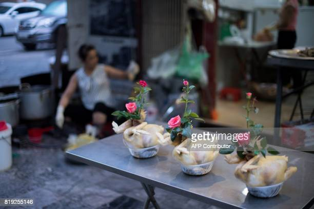Cooked Chickens for sale are adorned with pink roses as they are displayed in front of a food shop in the old quarters in Hanoi on July 20 2017 / AFP...