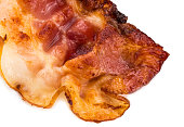 cooked crispy slice of bacon isolated on white background. close up.