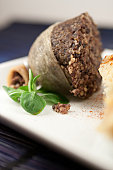 Apetising half haggis cooked presented  on a plate with a piece of lamb's lettuce