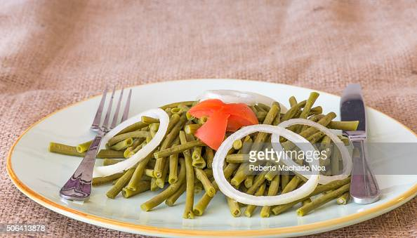 Cooked long Chinese green beans Delicious salad that only uses oil and vinegar as dressing The plate is garnished with a star of tomato and white...