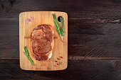An overhead photo of a slice of cooked meat, beef fillet, shot from above on dark rustic textures with sprigs of rosemary, salt, pepper, and a place for text