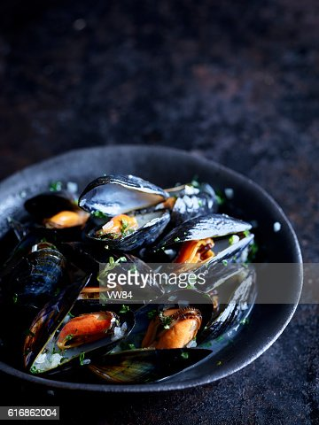 Cooked mussels in a black owl : Stock Photo