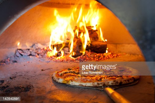 Cooked pizza coming out of hot brick oven : Foto de stock