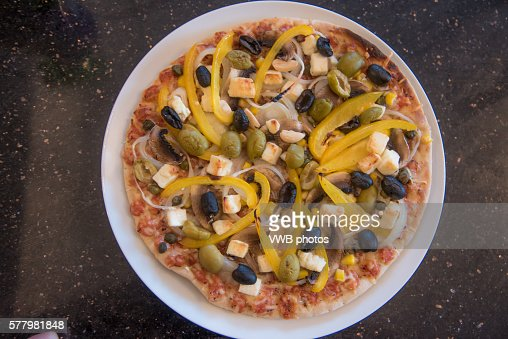 Cooked pizza on a plate with feta cheese, onion, pepper and green and black olive topping