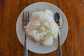 Cooked rice in a Plate and spoon on a table background.