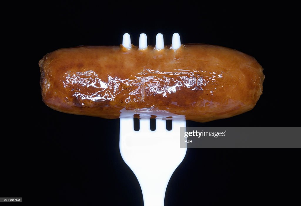 Cooked sausage on white plastic fork, close-up : Stock-Foto