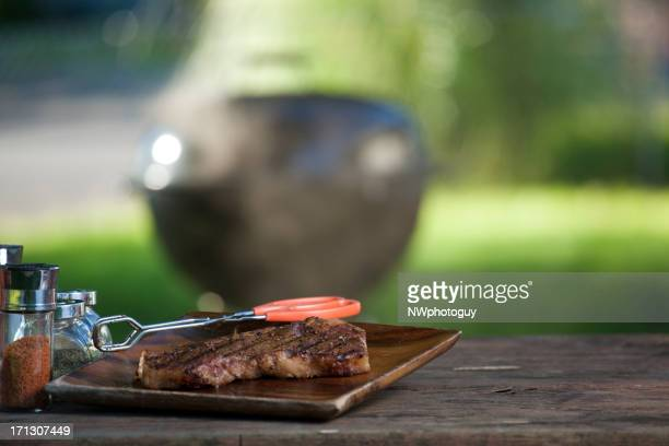 Cooked steak on a wooden board with grill in background