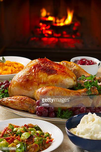 Cooked turkey on a dish with grapes in front of open fire
