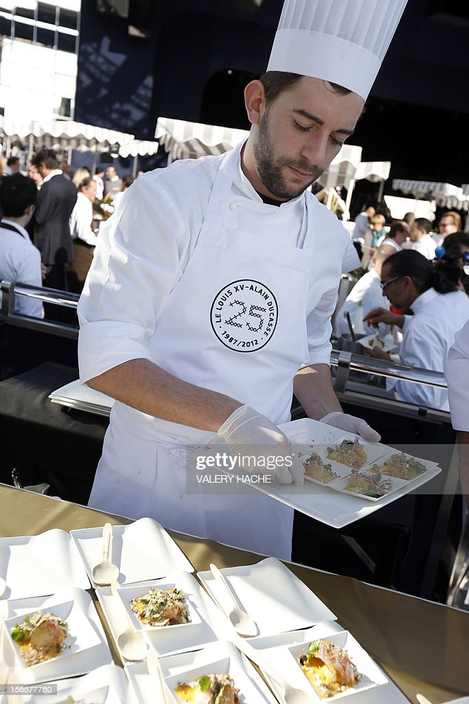 A cooker serves people at an ephemeral market during the festivities marking the 25th anniversary of French chef Alain Ducasse's restaurant 'Le Louis XV', on November 17, 2012 in Monaco.