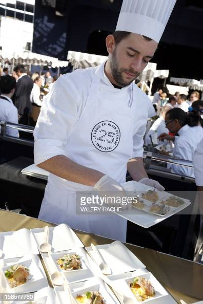 A cooker serves people at an ephemeral market during the festivities marking the 25th anniversary of French chef Alain Ducasse's restaurant 'Le Louis...