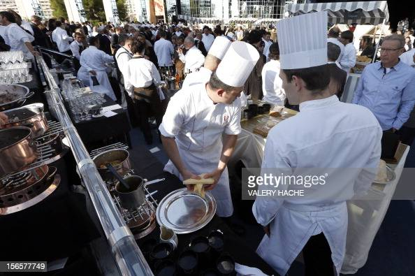 Cookers serve people at an ephemeral market during the festivities marking the 25th anniversary of French chef Alain Ducasse's restaurant 'Le Louis...
