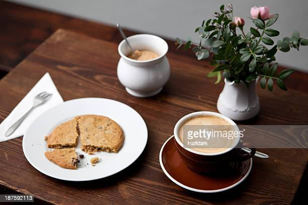 A cookie, cafe latte, jar of sugar and a vase of flowers on a table in a coffee shop