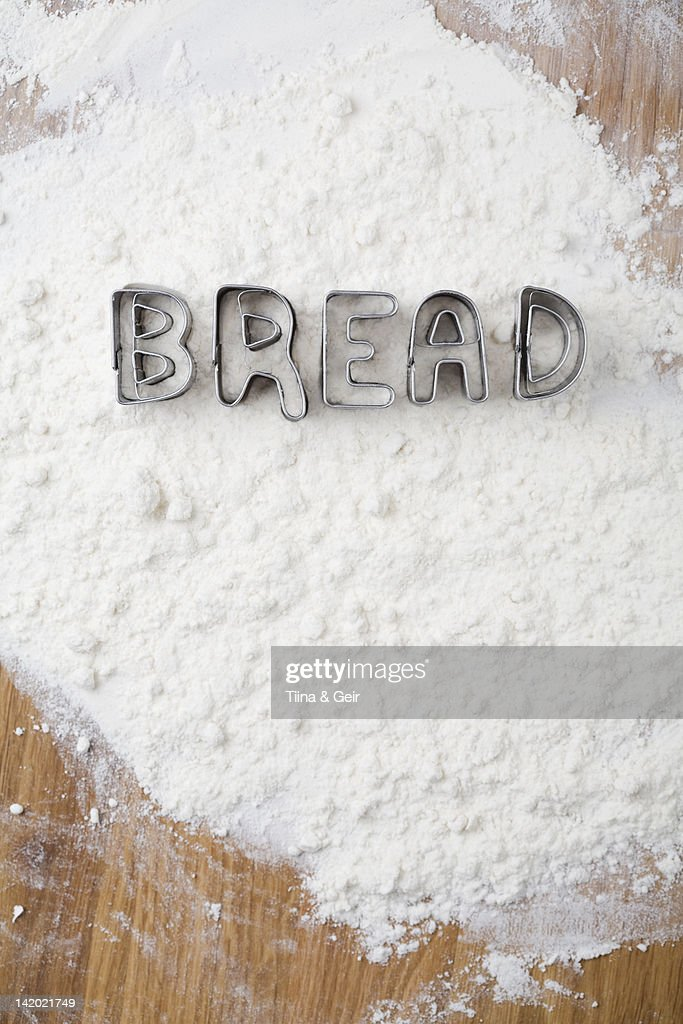 Cookie cutters spelling bread in flour : Stock Photo