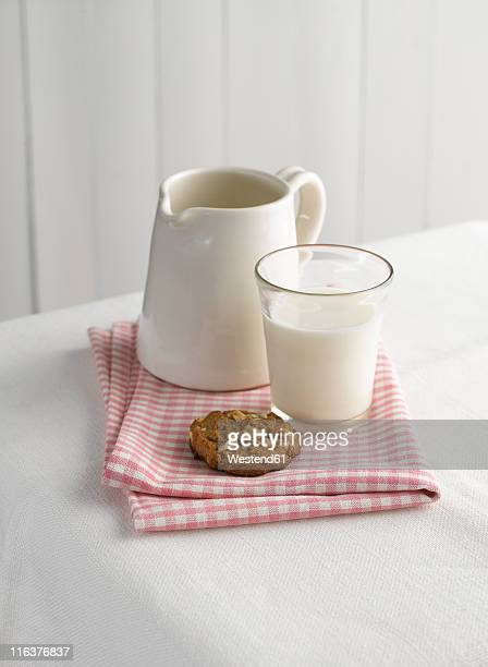 Cookie, milk and pitcher on napkin