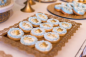 Cookies with blue and golden decoration on golden tray. Cookies decorated with crowns and angels. Ideal for religious celebrations or boys party decoration