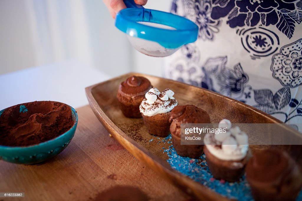 cooking cupcakes, muffins and a plate of ingredients for decoration : Stock Photo