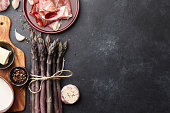 Bunch of fresh purple asparagus cooking with bacon, garlic and spices on rusty textured background