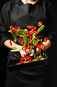 Cooking fresh vegetables in the pan chef. Vertical viewing of photos. Dark black background
