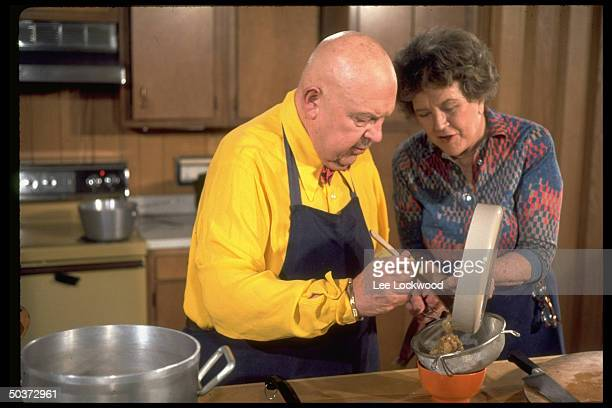 Cooking gurus Julia Child and James Beard engrossed in activity w frypan and strainer at a stove while appearing on TV program Revoutionary Recipes
