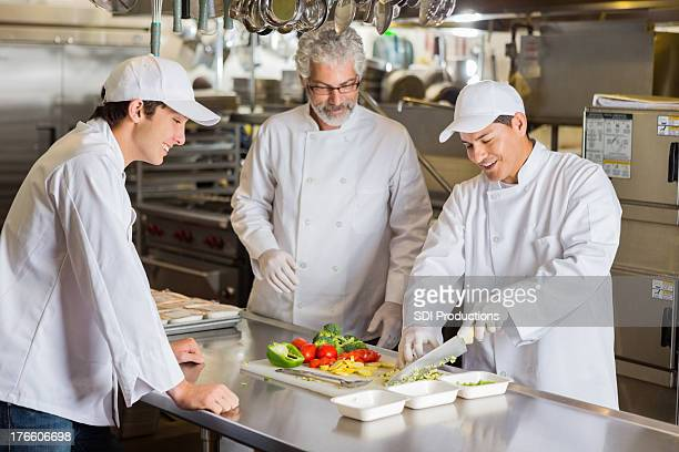 Cooking instructor teaching culinary students in commercial kitchen