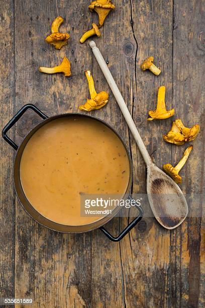Cooking pot of cream of chanterelle soup, wooden spoon and chanterelles on dark wood
