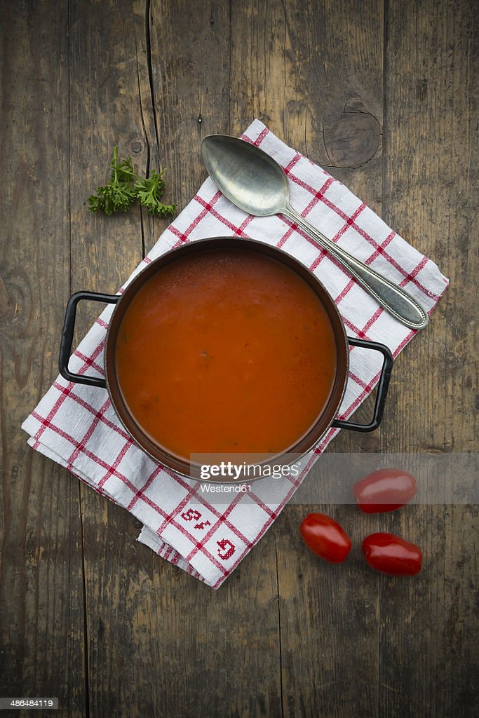 Cooking pot of tomato soup on kitchen towel and wooden table