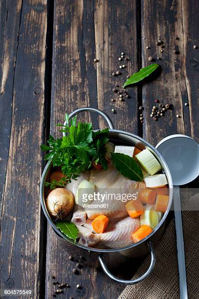 Cooking pot with raw corn-fed chicken, onion, herbs and greens