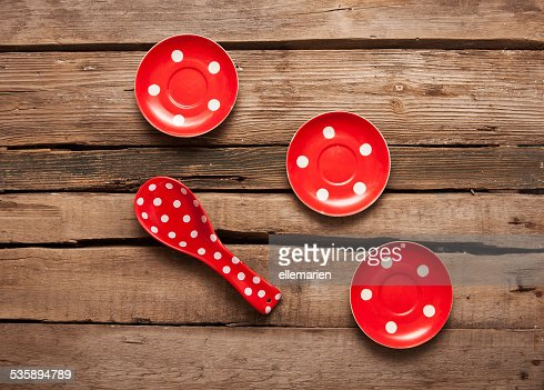 cooking red spoon and plates with polka dots, wooden background : Stock Photo