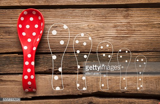 cooking red spoon with polka dots on wooden background : Stock Photo