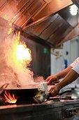 Chef preparing food in a pan in flames.