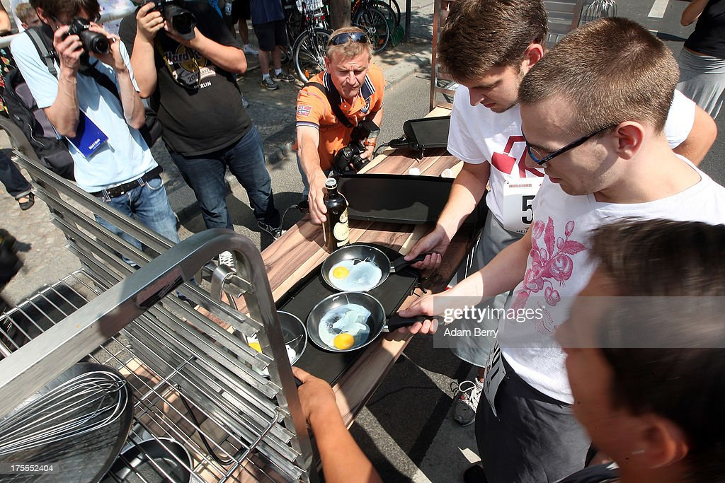 Cooks fry eggs during a stage in their run during the Waiters' Derby (Kellner Derby in German) on August 4, 2013 in Berlin, Germany. At the annual event, brought back into existence in 2011 on the 125th anniversary of the Kurfuerstendamm (known locally as the Ku'damm), a main shopping thoroughfare, waiters, porters, cooks and bartenders run a 400-meter track while performing their regular occupational duties. The event was reinstated after a hiatus since the 1950s, when it was created to bring a sense of normal life back to Berlin after World War II under the Allies, a period in which gastronomical interest in the isolated Western part of the city suffered.