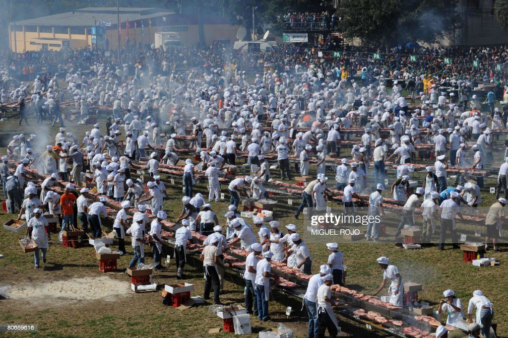 Cooks grill beef in a 1,500 meter long broiler during 'The World' s Biggest Barbecue', an event in which 12,000 kg of beef will be grilled to break the Guinness record in Montevideo on April 13, 2008. AFP PHOTO / Miguel Rojo