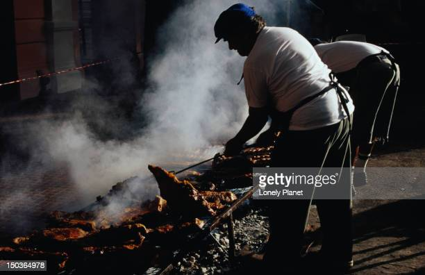 Cooks turning over beef cuts on open-air grill on Plaza del Resero during Feria de Mataderos, Mataderos.