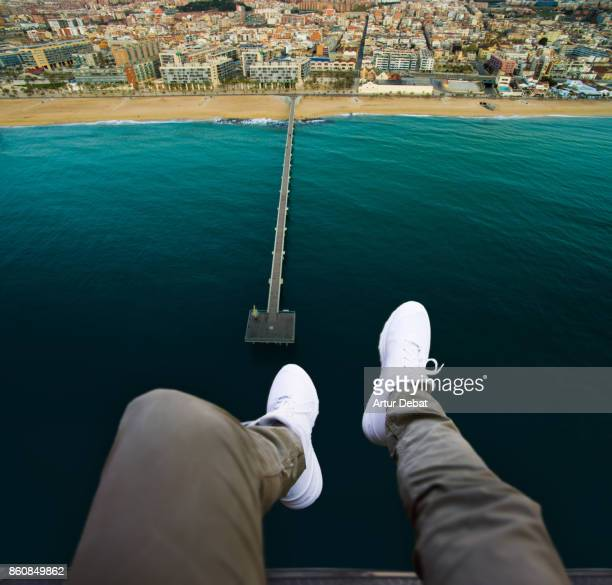 Cool aerial view from helicopter of guy with white shoes and legs from personal perspective over the view of a nice pier and beach in the Mediterranean sea.