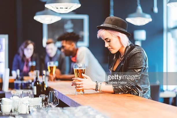 Tendance jeune femme blond boire de la bière dans un pub