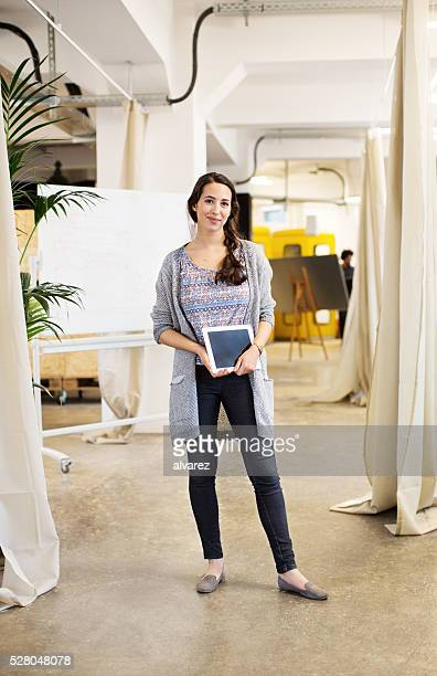 クール女性実業家保持デジタルタブレットを備えたオフィススイート、