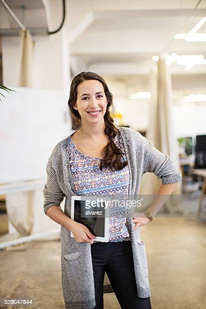 Cool businesswoman holding digital tablet