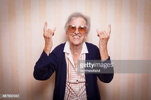 cool elder lady making rock on sign : Stock-Foto