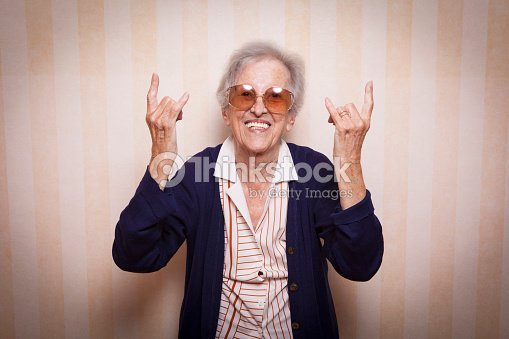cool elder lady making rock on sign : Stock Photo