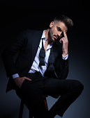 cool elegant man in tuxedo having a headache , he sits on a chair with hand in pocket and fingers on forehead; modern pensive young man